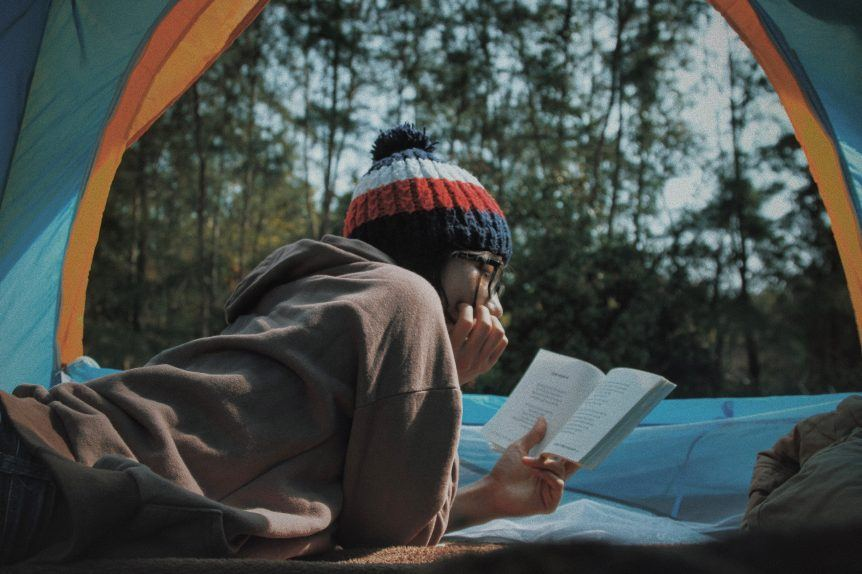 Woman camping while reading a book